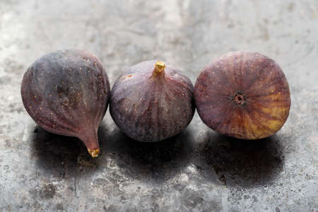 whole ripe fresh three figs on a black table. close-up. the fruit texture is clearly visible Banque d'images - 129475711