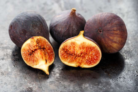 whole and sliced ripe fresh figs on a black table. close-up. the fruit texture is clearly visible Banque d'images - 129475724
