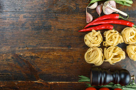 uncooked tagliatelli spaghetti on a brown wooden background. set with vegetables. place for text
