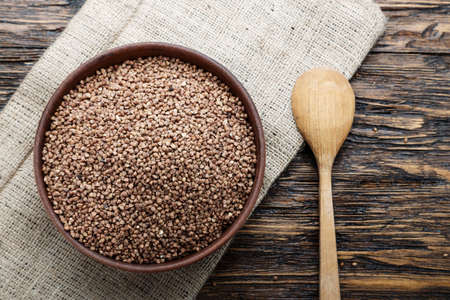 raw buckwheat in a clay plate, on a burlap napkin, on a wooden background. view from above. nearby lies a spoon. place for text
