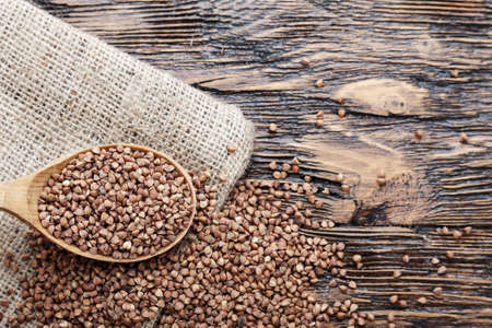 raw buckwheat is scattered on a table on a burlap napkin. nutritious and dietary cereals