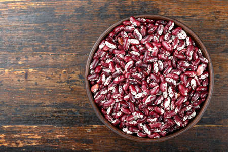 raw beans in a plate on a wooden background. place for text. view from above