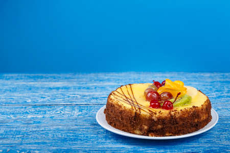 whole cake with cream and fruit on a blue background. place for text