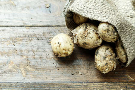 dirty young potatoes on the table, on wooden background, in burlap. place for text Stok Fotoğraf