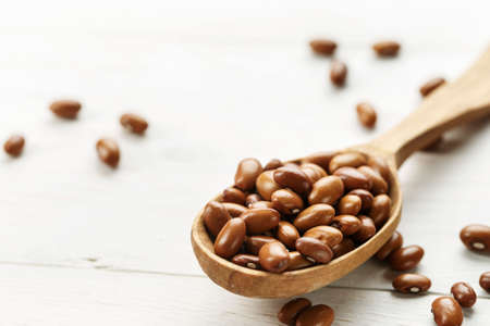 brown raw beans in a wooden spoon on a wooden background