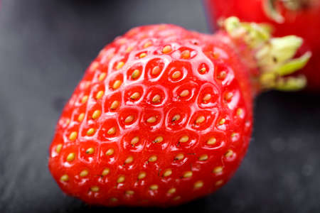 one ripe strawberry close-up on a black background. clearly visible texture of berries