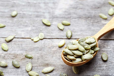 pumpkin seeds in a wooden spoon on a wooden background. view from above. place for text Stock Photo