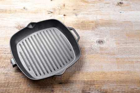 New empty cast-iron grill pan with two handles on a wooden background. place for text