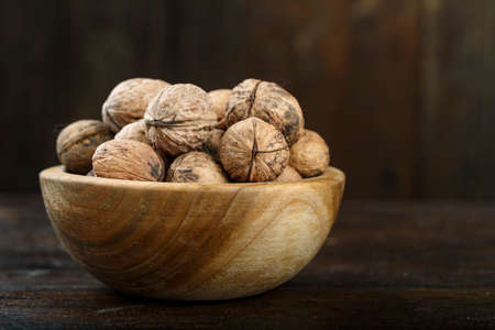 inshell walnuts in a plate on a wooden background. nutritious vegan product