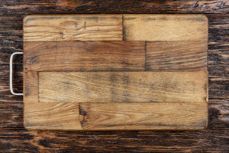 Rectangular cutting wooden board on a brown wooden background. place for text  Stock Photo