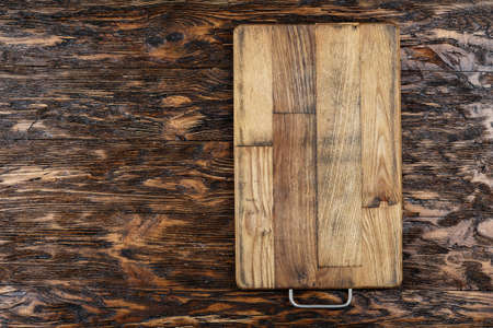 Rectangular cutting wooden board on a brown wooden background. place for text Фото со стока - 131364472