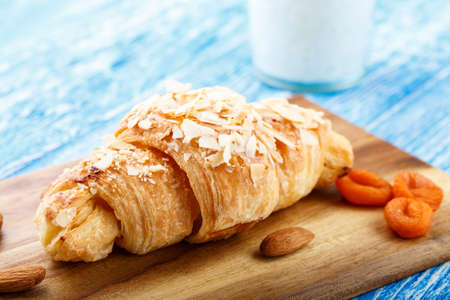 Fresh croissant and dried fruits on the table. traditional carbohydrate breakfast  Stock Photo