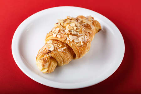 croissant in a plate on a table on a bright red background. traditional french breakfast