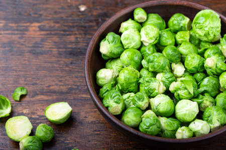 raw brussels sprouts in a clay plate on a wooden background. place for text