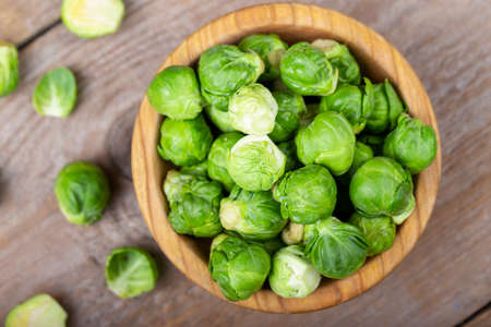 raw brussels sprouts in a plate on a wooden background. place for text