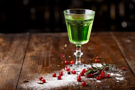 green cocktail on the basis of absinthe in a stylish vintage glass on a brown wooden background. white sugar and cranberries are scattered nearby
