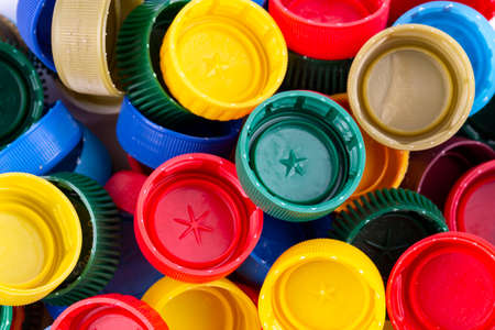multicolored plastic bottle caps are scattered as a background. place for text Stockfoto