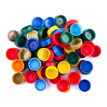 multicolored plastic bottle caps are scattered on a white background. place for text