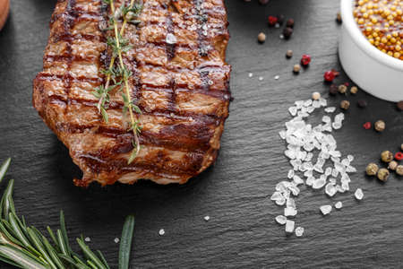 fresh beef steak with spices on a black background. place for text