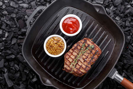 fresh beef steak with spices in a grill pan. place for text