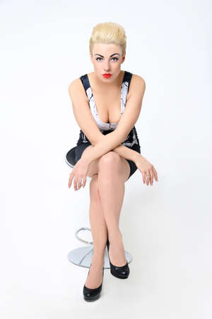 The sexy girl in rock style sits on a chair on a white background. blonde with red lips. studio photo Banco de Imagens
