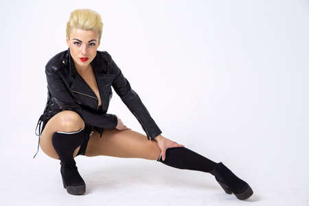 sexy girl in rock style on a white background. blonde with red lips. studio photo