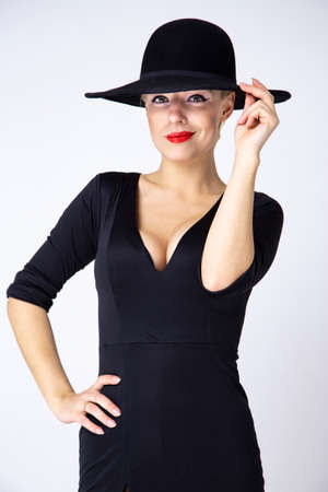 fatal sexy girl in a black hat and black dress with a neckline on a white background.