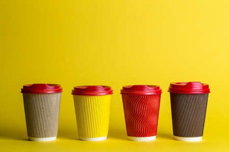 many different types of coffee in paper glasses on a yellow background, space for text
