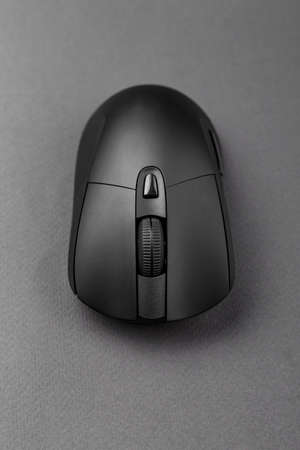black wireless computer mouse on a black background. modern office equipment