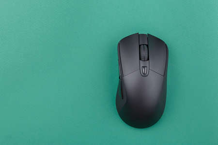 black wireless computer mouse on a green background. modern office equipment. place for text