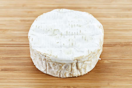 mug of brie cheese on a wooden background. place for text