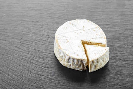 Camembert cheese circle on a black background. place for text