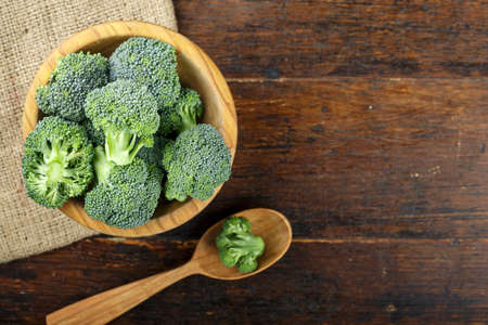 raw broccoli on a table in a wooden plate, on wooden background. rustic vegetable background