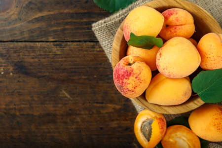 ripe apricots in a plate on a brown wooden background. place for text  스톡 콘텐츠