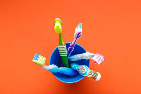 different toothbrushes stand in a glass on a bright background. oral care. place for text