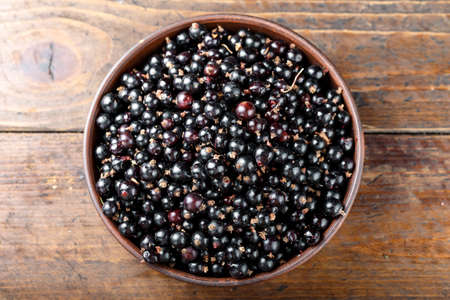Fresh currants in a clay plate on a brown wooden table. harvest of vitamin berries Stock Photo - 133335284