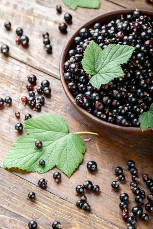fresh currant with green leaves in a clay plate on a brown wooden table. harvest of vitamin berries  Banco de Imagens