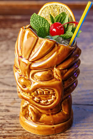 Exotic cocktail in tiki glass rum runner decorated with cherry, mint and orange slice in a ceramic glass