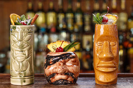 Set of three tropical cocktails in tiki glasses in a nightclub on the background of a bar counter. Long alcoholic cocktails with ice, rum and various kinds of fruit juices