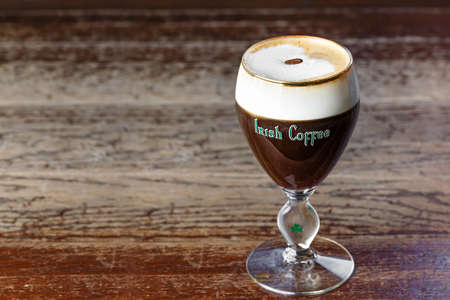 Caffè irlandese con whisky. Cocktail alcolico riscaldante con schiuma di panna e chicchi di caffè su di esso. Bevi al bar o al ristorante