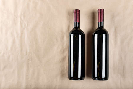 two bottles of wine on a light paper background. craft paper under the wine. place for text