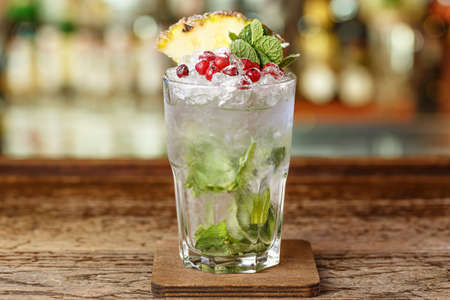 Cocktail with ice on the bar, refreshing drinkslong with mint and brandy, garnished with cranberries and pineapple. Space for text