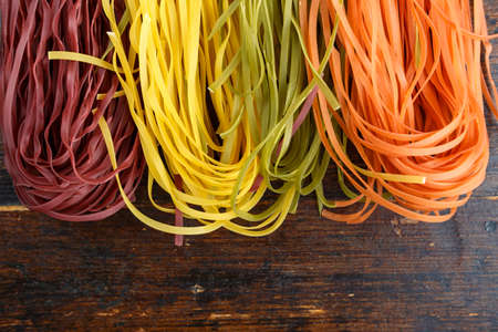 multi-colored long spaghetti. traditional italian pasta on a wooden background. place for text