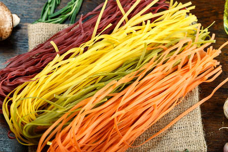 multi-colored Italian pasta. set of raw spaghetti with vegetables and spices on a brown wooden background