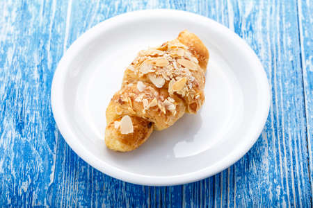 traditional french breakfast. croissant in a plate on a blue wooden background