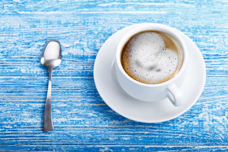 coffee with milk in a cup on a shabby blue background. place for text Banco de Imagens