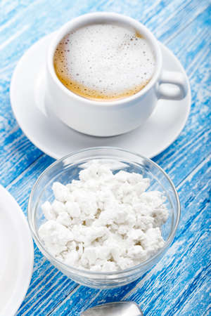 coffee with milk in a cup and cottage cheese on a shabby blue background. place for text Banco de Imagens