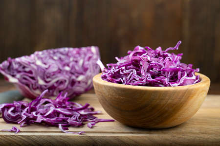 finely chopped purple cabbage in a wooden plate. on a brown wooden background. place for text Banco de Imagens