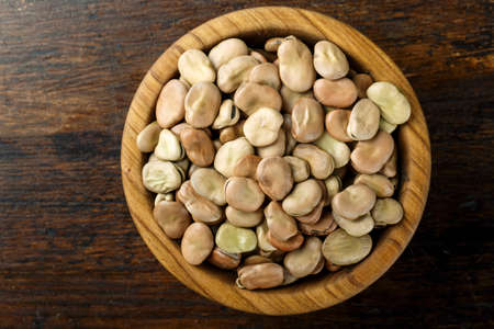 raw broad beans in a wooden plate on a wooden background. place for text. bean texture clearly visible