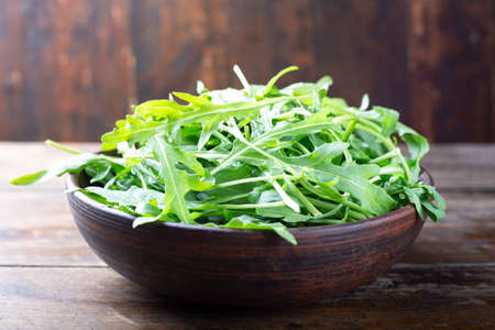 Fresh green arugula salad on a table in a clay plate. simple rustic background 免版税图像